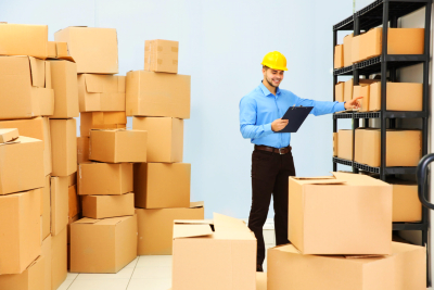 Man holding clipboard and pointing on cartoon box at warehouse